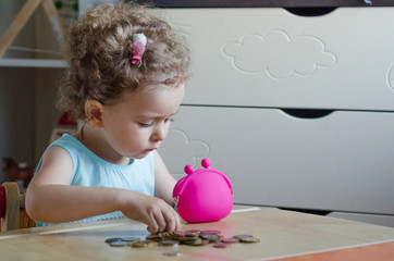 People, money, finances and savings concept.  happy little girl putting money into the wallet.children and finances. financial literacy. budget allocation.  copy space. soft focus.