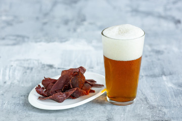 Glass of beer on the white stone table background. Cold drink and meat snacks are prepared for a big friend's party. Concept of drinks, fun, food, celebrating, meeting, oktoberfest.