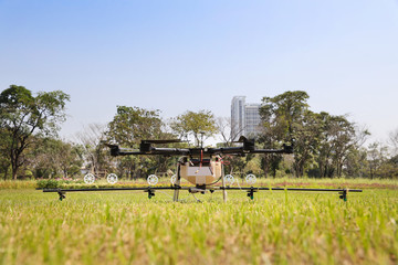 front view picture of drone on green grass for sprinkle water from the air for causing dust to drop and reduce PM 2.5 in Thailand