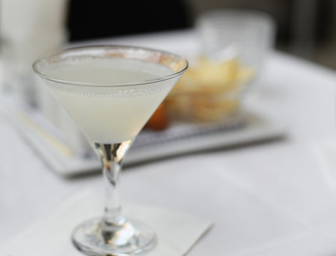 White lady gin cocktail in martini glass with crisps in the back. Very selective focus