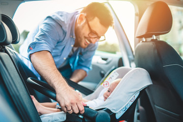 Young father putting his baby boy on a safety child car seat.