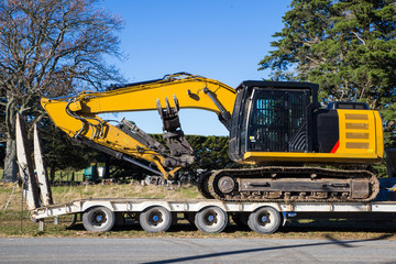 A large yellow digger is is delivered by transporter truck to a works site in Canterbury, New Zealand