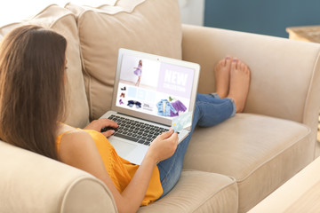 Fototapeta Young woman shopping online with credit card and laptop at home obraz