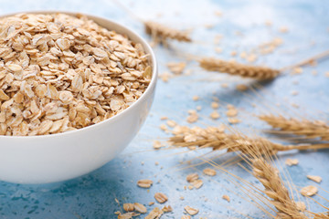Bowl with raw oatmeal on color background, closeup