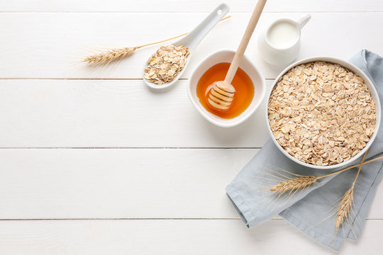Bowl with raw oatmeal, honey and milk on white wooden table