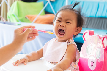 Asian baby girl crying to have food