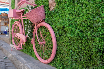 Old pink basket bike standing on pavement. It's attached to the wall.