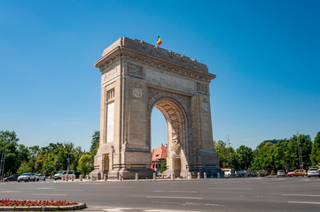 Poster de jardin Europe de l Est Triumphal Arch, Eastern european landmark and travel destination concept theme with the Arch of Triumph (Arcul de Triumf) in Bucharest (capital city of Romania) against cloudless sky on a summer day