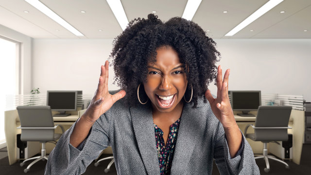 Black African American businesswoman in an office looking angry.  She is an owner or an executive of the workplace.  Depicts careers and startup business.