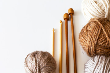 Wooden needles for hand knitting, crochet hooks and a brown balls of wool yarn on a white background. Still life, place for text, close up, flat lay