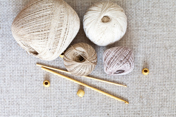 Cotton and linen natural yarn in balls for hand knitting. Wooden hooks and beads on the background of the canvas. Crafts and Hobbies. Тоp view, close up, flat lay, still life