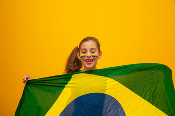 Football supporter, Brazil team. World Cup. Beautiful little girl cheering for her team on yellow background Fototapete