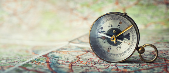 Fototapete - Magnetic old compass on world map.Travel, geography, navigation, tourism and exploration concept wide background. Macro photo. Very shallow focus.