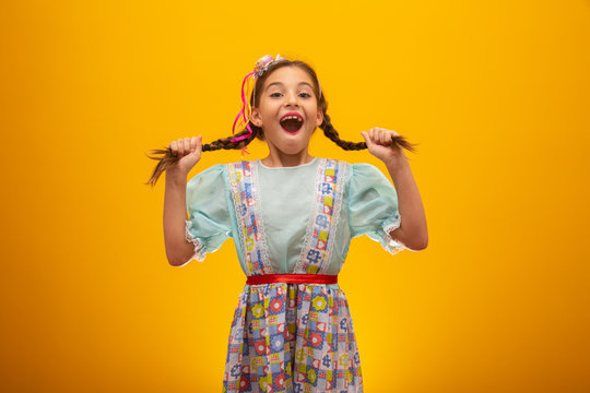 """Child in typical clothes of famous Brazilian party called """"Festa Junina"""" in celebration of São João. Beautiful girl on yellow background."""