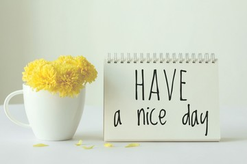 Have a nice day note on paper with yellow in white cup of coffee on white background.minimal style.