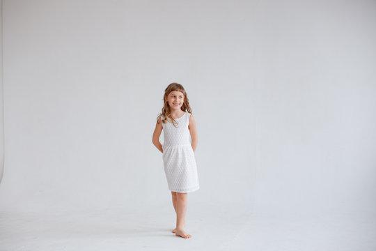 girl in white dress dancing on white background