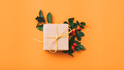 Gift delivery service. Top view of beige handmade paper box with rose hip decor on vibrant orange background. Copy space.