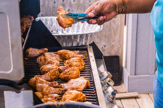 African American Nigerian man grilling roasting chicken thighs on Barbeque