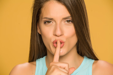 Young woman with finger on her lips on yellow background