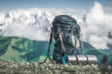 Tourist backpack and sleeping pad on a background of mountains