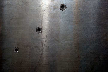 Old scratched steel background with bullet holes