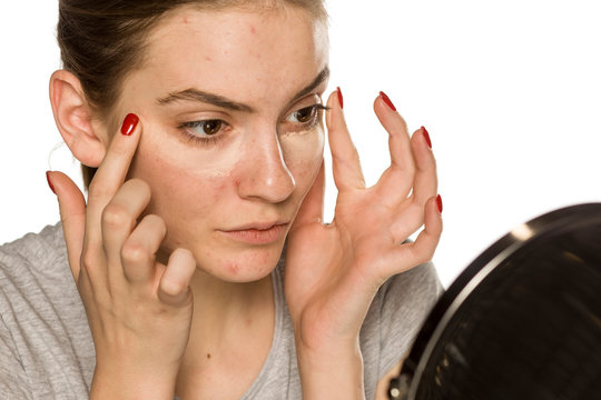 Young woman applying concealer with her fingers on white background