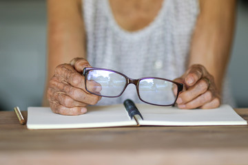 Old woman hands holding eye glasses on wooden table and notebook