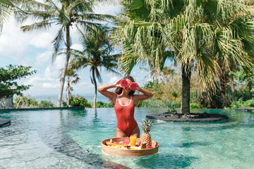 Cheerful young woman covering eye with half of fresh ripe pitahaya, dragon fruit , standing in the swimming pool with floating breakfast in luxury hotel