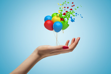 Side closeup of woman's hand facing up and holding tiny bundle of colorful balloons that are dissolving in pieces on top on light blue background.
