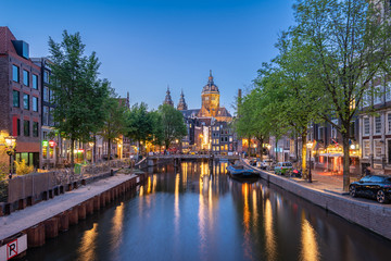 Night in Amsterdam city with Saint Nicholas Church at night in Amsterdam, Netherlands