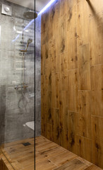 Modern glass frameless shower cubicle with wooden wall and floor in bathroom interior, copy space