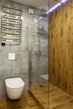Modern bathroom interior with glass shower cubicle, toilet and wood wall and floor, copy space