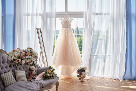 Beautiful beige wedding dress hanging on hanger against window in hotel room, copy space. Bridal bouquet and women's shoes standing on chesterfield sofa