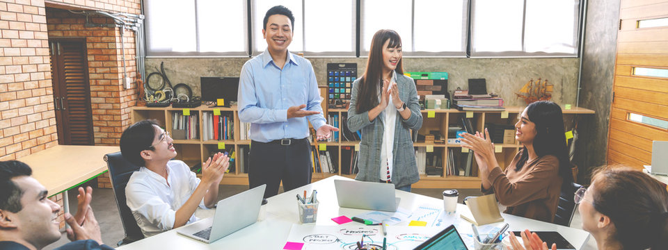 Millennial boss team leader introducing New asian woman employee to colleagues in creative office workplace. Welcoming hired newcomer member to team. first work day get claping hands with colleagues.