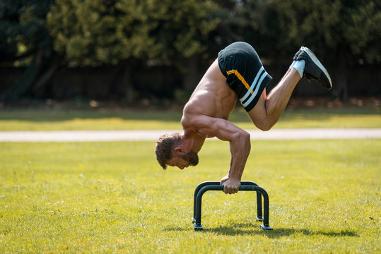 calisthenics hand stand fitness, sport, training and lifestyle concept - young man exercising on parallel bars outdoors