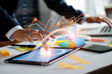 Businessman using tablet and laptop analyzing sales data and economic growth graph chart. Business strategy. Digital marketing. Business innovation technology concept Wall mural