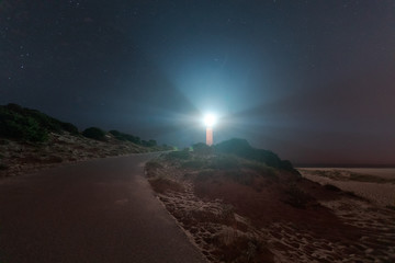 Foto op Plexiglas Zwart Trafalgar lighthouse under a sky full of stars, at Caños de Meca at Cadiz region, Andalucia, Spain.