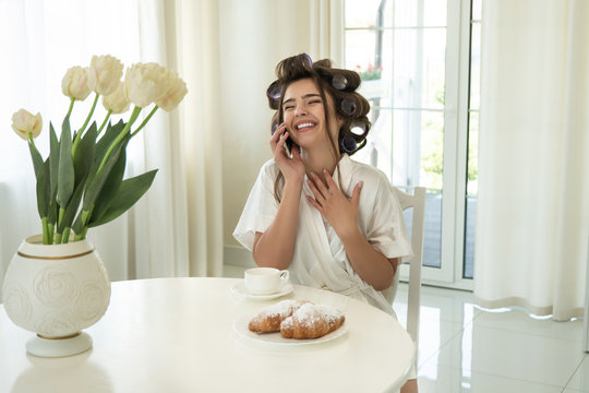beautiful young smiling brunette woman in hair curlers speaking on smartphone while drinking coffee and eating croissants for breakfast in bright kitchen