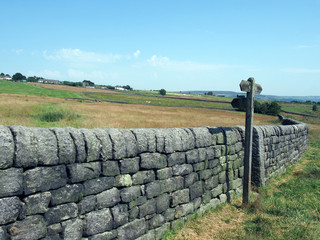 rural scene with a long stone wall and wooden signpost next to a gate in hillside meadows with farmhouses and hills in the distance in blackshaw head in west yorkshire