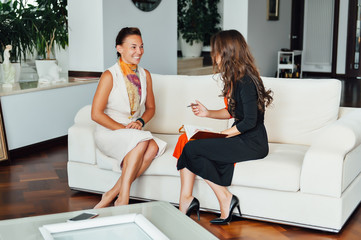 Smiling woman talking with a coach to find the motivation to achieve the goals of financial success