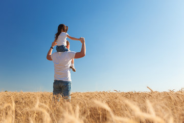 Happy father and daughter walk in the summer field. Nature beauty, blue sky and field with golden wheat. Outdoor lifestyle. Freedom concept.