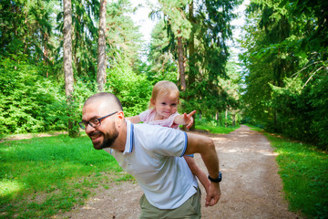 man playing with his little daughter in the nature