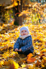 smiling baby girl sitting in yellow leaves
