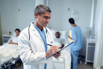 Male doctor writing on clipboard in the ward at hospital