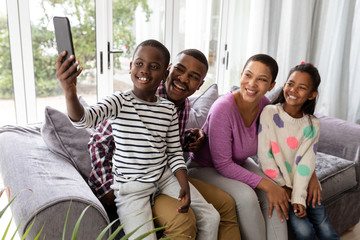 Family taking selfie with mobile phone on a sofa in living room