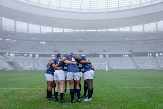 Group of male rugby players forming huddles in the morning