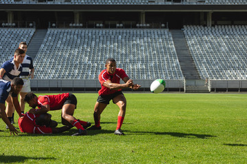 Male rugby players playing rugby match in stadium