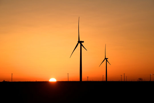Wind turbines operate at sunrise in the Permian Basin oil and natural gas production area in Big Spring