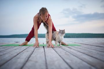 Beautiful young woman practices yoga asana Prasarita Padottanasana on the wooden deck near the lake