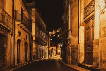 Narrow typical italian street of baroque city Ragusa Ibla at night, Sicily, south Italy